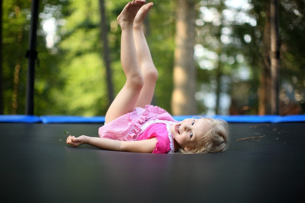 A little girl playing on trampoline
