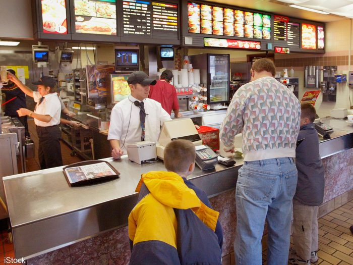 The father, his teen and a younger child are in a fast food chain. Do you think foods here are healthy to eat and rich in vitamins?