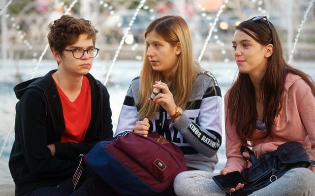 Teenagers talking at the park. They could be talking about vitamin that supports energy muscle skin immunity 60 servings.