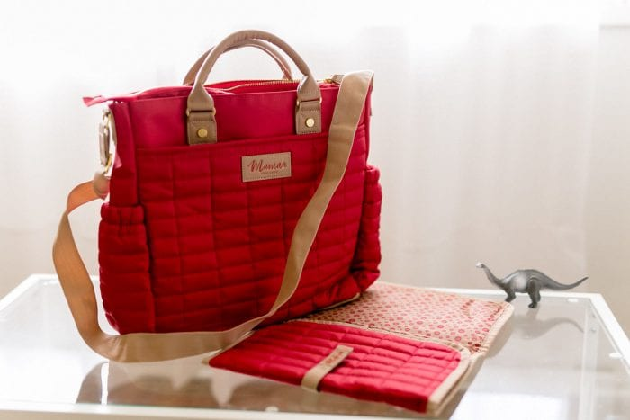 A red mom purse with exterior pockets, leather top handle handbag, crossbody strap and main compartment inside