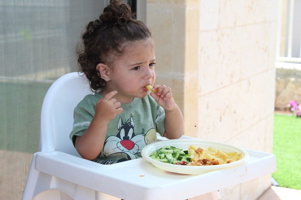 Baby eating some healthy food. Eating the right foods along with child vitamin supplements can help in gaining weight