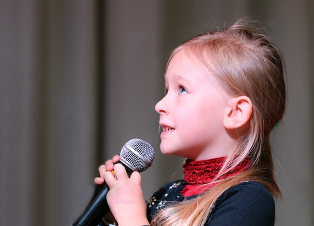 A Kid singing using a children's microphone.
