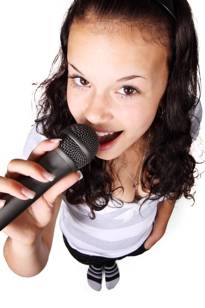 Older child singing using a kid's microphone.