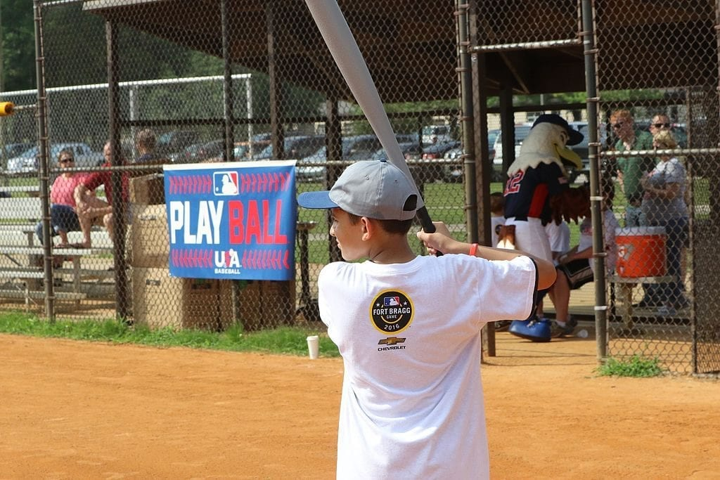 An 11 year old boy holding a baseball bat. It is a good gift for 11 years old.