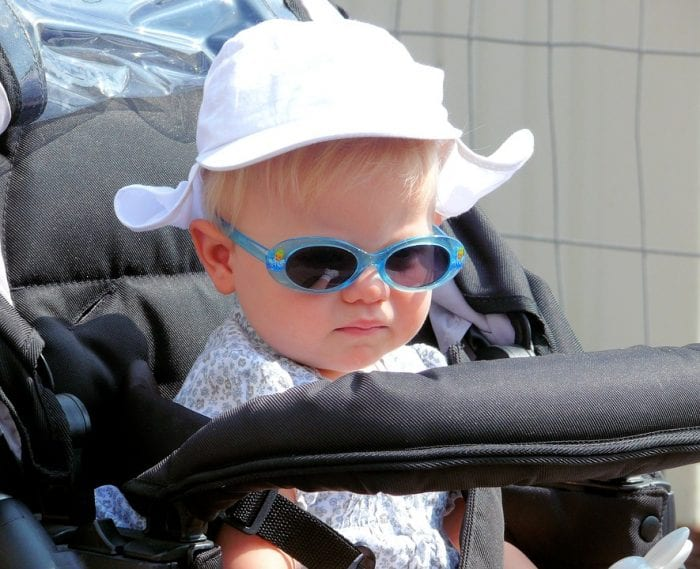 A baby sitting on a kolcraft stroller. Can you recognize if it is a kolcraft cloud plus or sport?