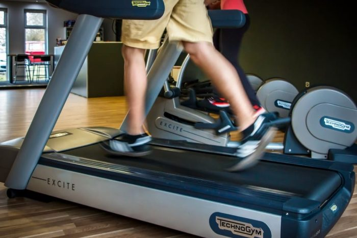 Man running on a TechnoGym treadmill. Check out the best treadmills under $300 for house gym set up.