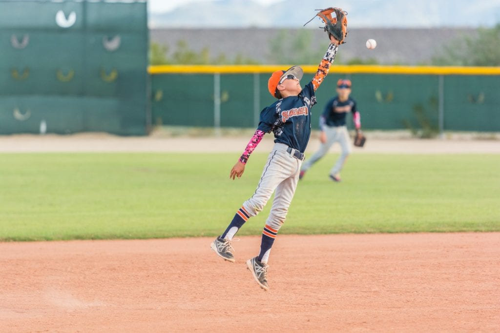 A kid playing baseball and wearing a baseball cleat. Find out the difference between soccer and baseball cleats.