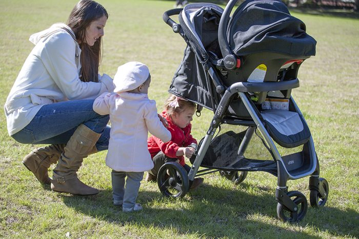 A mother using an Urbini stroller for her child. This Urbini has stroller, carseat with base.